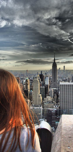 Rear view of red-haired woman looking at new york city buildings