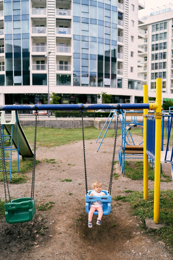 People sitting on swing in playground