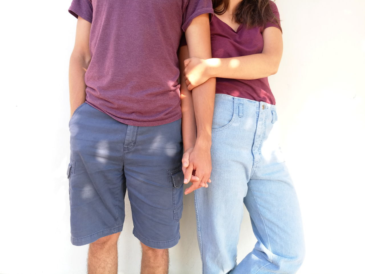 Midsection of couple holding hands against white wall