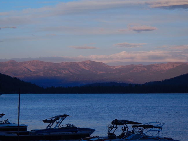 The Sierra Nevada Range over Donner Lake at dusk. View from Donner Lake Marina. Beauty In Nature Boat Calm Cloud - Sky Dusk Idyllic Lake Lakeshore Landscape Majestic Mode Of Transport Mountain Mountain Range Nature Non-urban Scene Scenics Sky Tourism Tranquil Scene Tranquility Transportation Travel Vacations Water