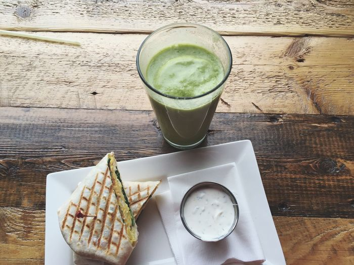 High angle view of coffee and wrap sandwich on table