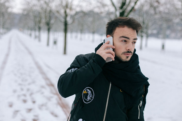 Man talking on mobile phone against trees during winter