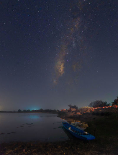 Rowboat On Lakeshore Against Star Field Sky