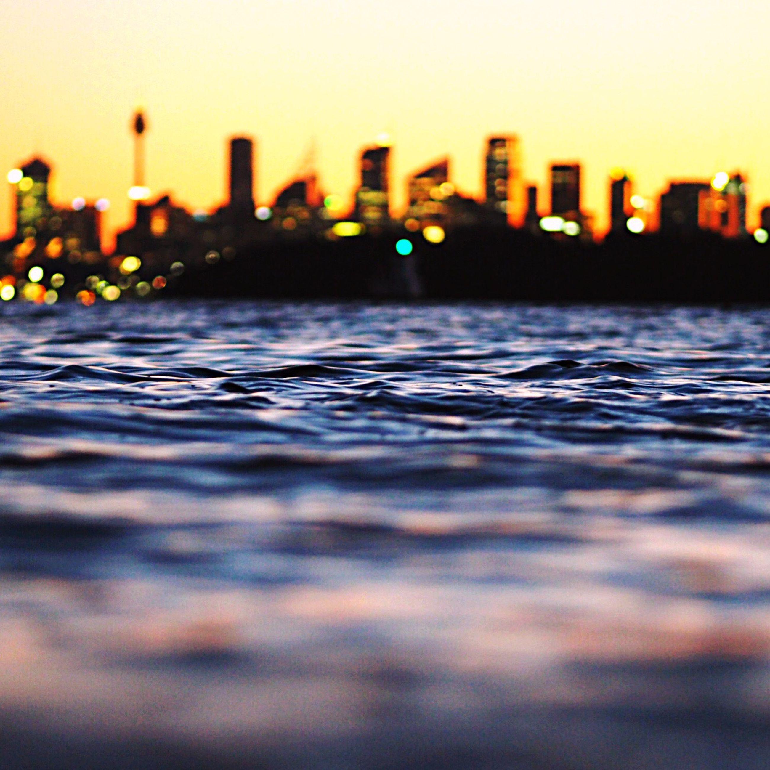 surface level, sunset, selective focus, illuminated, building exterior, sky, outdoors, city life, the way forward, waterfront