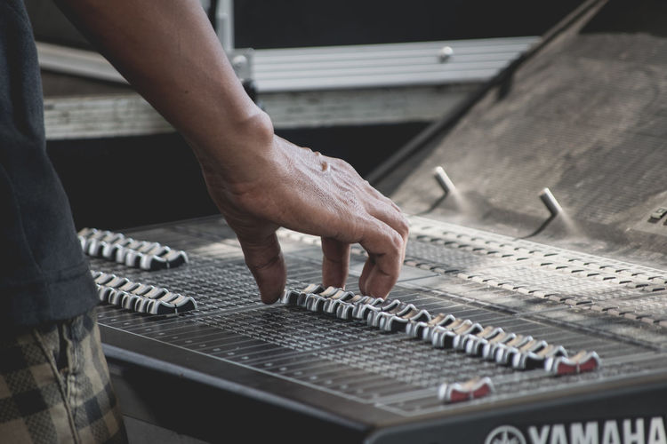 Cropped image of man using sound mixer in studio