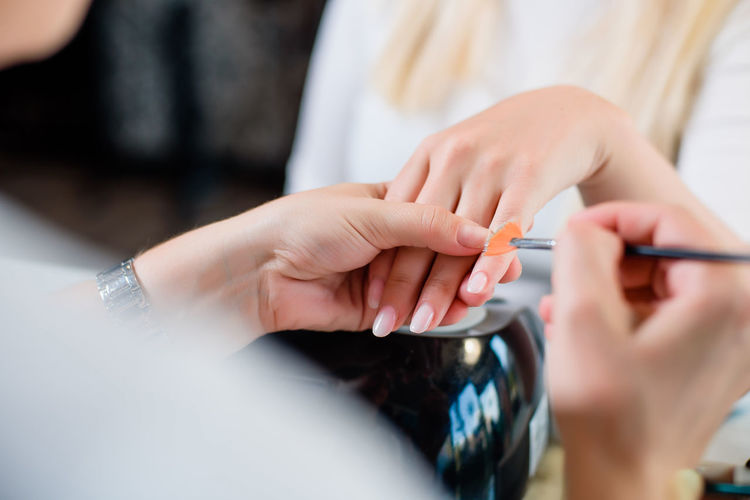 Close-Up Of Stylist Painting Woman Nails At Salon