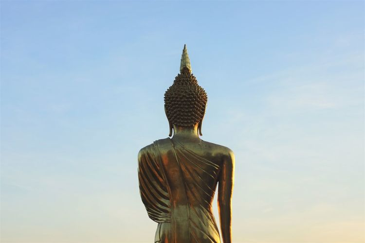 Low angle view of golden budda statue against sky