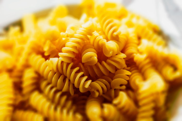 High angle view of pasta in plate Cooking Dinner Food Lunch Macaroni Pasta Carbohydrate Closeup Cuisine Culture Health Ingredients No Person Noodles Nutrition Penne Spaghetti Still Life Traditional Wheat Freshness Close-up Yellow Flower Selective Focus Flowering Plant No People Indoors  Beauty In Nature Petal Food And Drink Plant Vulnerability  Italian Food Flower Head Fragility Inflorescence Temptation