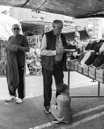 Grandad choosing shoes on Santa Pola market in Spain. Little boy is bored and not the slightest bit interested. Bored Boy Choosing Grandad Man Market Outdoors People Santa Pola Sat Seated Shoes SPAIN Stalls