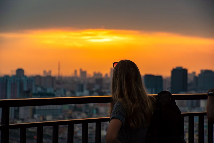 Rear view of woman looking at cityscape during sunset