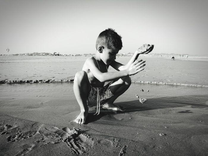 Full Length Of Boy On Beach Against Clear Sky