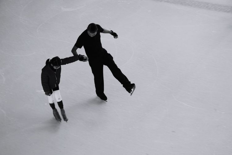 High angle view of father and son ice-skating on rink