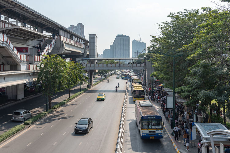 Vehicles on road amidst buildings in city against sky