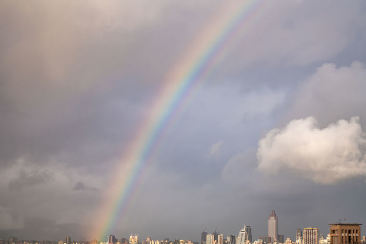 Low angle view of rainbow over buildings in city against sky