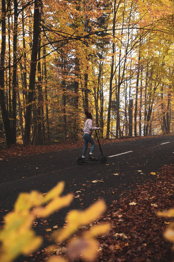 Full length of woman on push scooter in forest during autumn