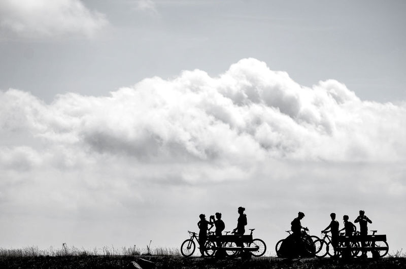 Silhouette people riding bicycle against sky