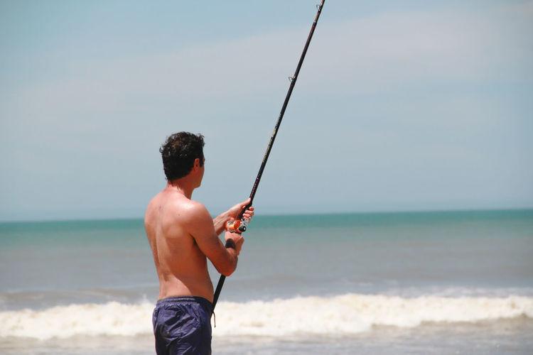 Man fishing at beach against sky
