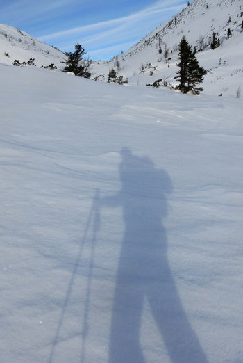 Shadow of person on snow covered field