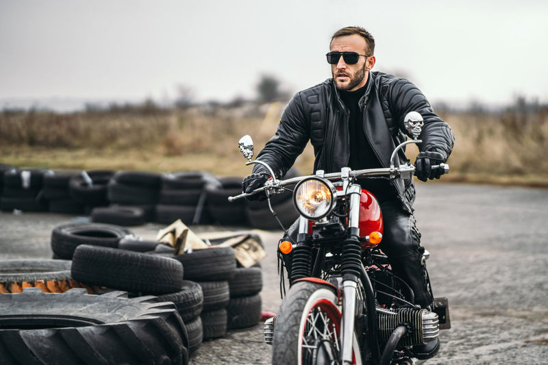 Man riding motorcycle on sunglasses against sky