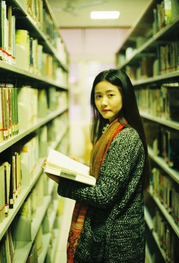 Side View Portrait Of Young Woman Holding Book In Library
