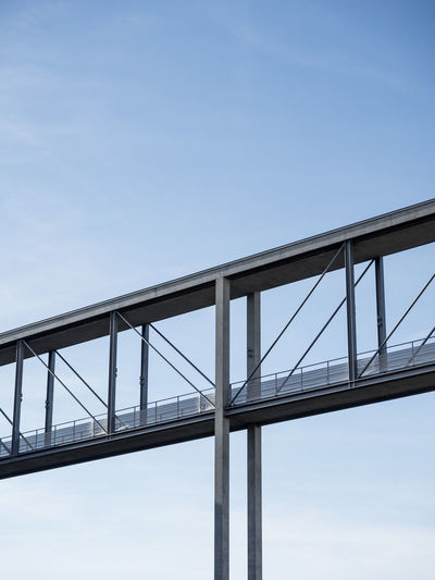 Low angle view of concrete foot bridge against sky