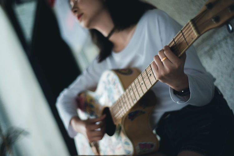Mid section of a woman playing guitar