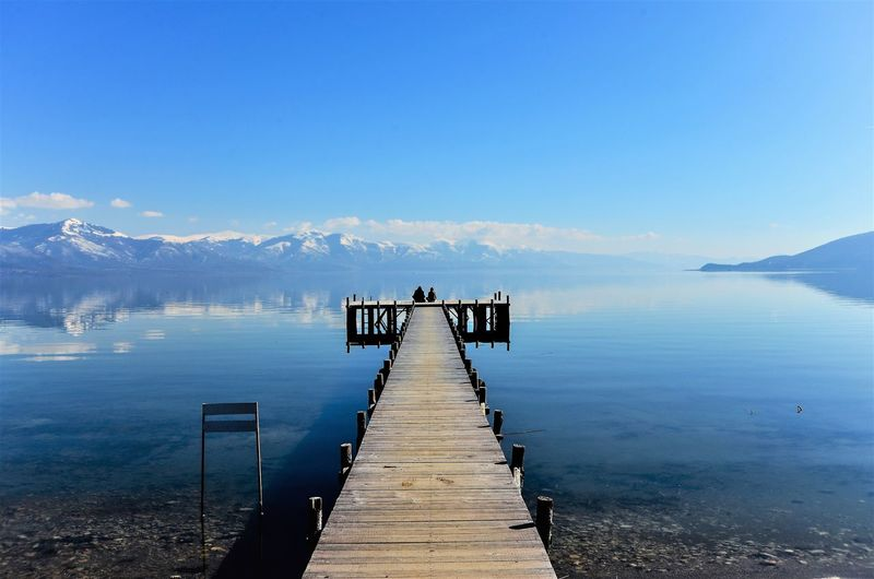 Jetty over lake against blue sky