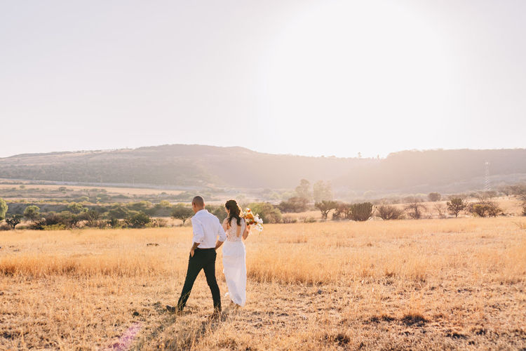 Couple standing on field against clear sky