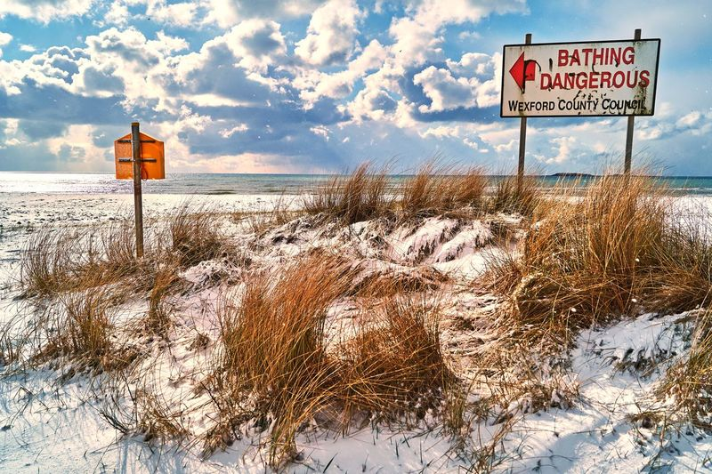 Information sign on snow covered landscape against sky
