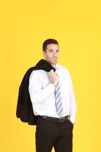 Portrait of man standing against yellow background