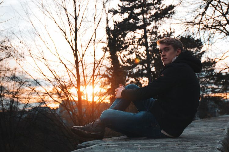 Side view of young man sitting on rock at sunset