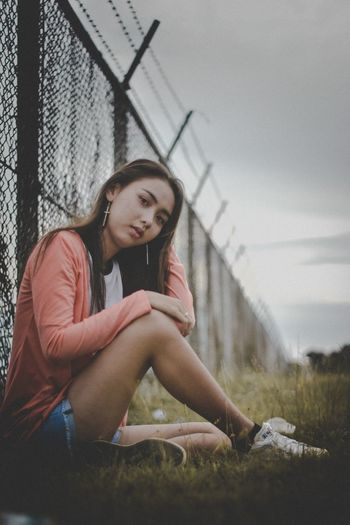 Full length of young woman sitting on bridge against sky