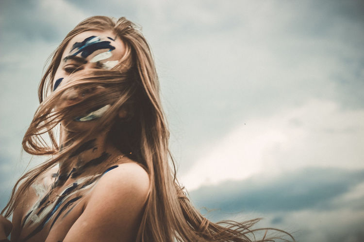 Portrait of young woman with face paint standing against sky
