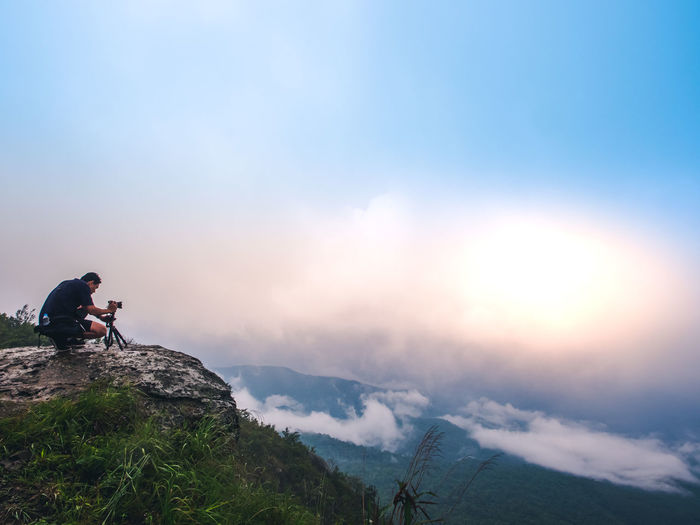Man sitting on rock against mountains against sky