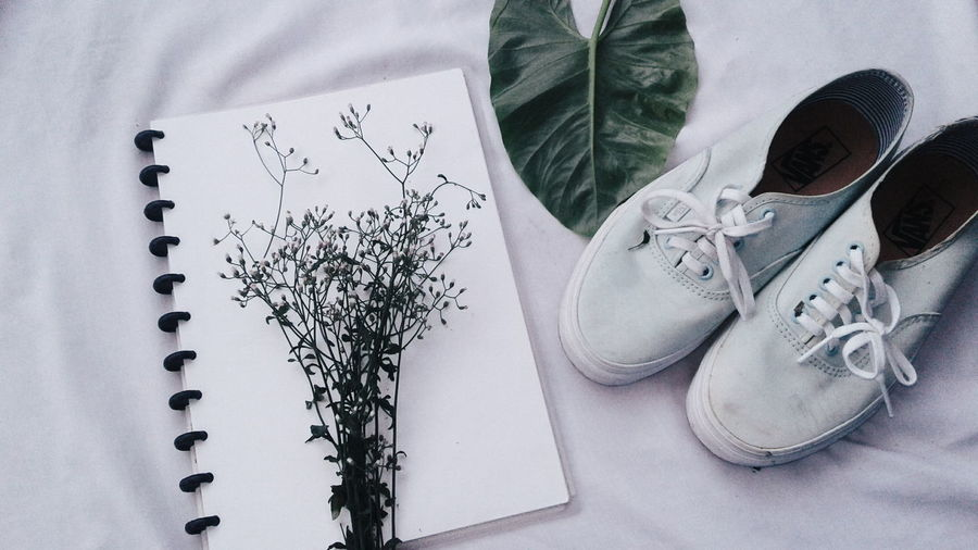 High angle view of book with shoes and plant on fabric