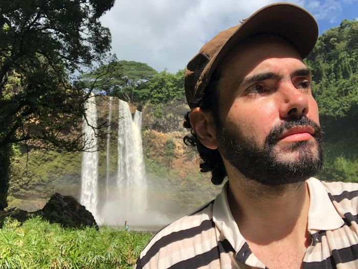 Portrait of man looking away against waterfall