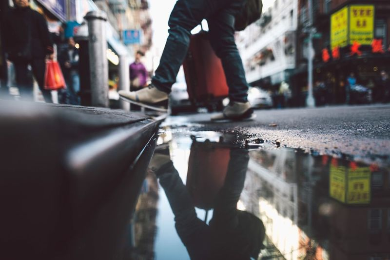 Low Section Of Man Standing By Puddle On Street
