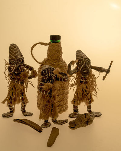 Three Afro-Brazilian Priests dancing to praise God Cachaça AFRICAN CULTURE Art And Craft Bottle Cachaça Close-up Creativity Day Dolls Indoors  No People Still Life Studio Photography Studio Shot Sunset White Background Wood - Material