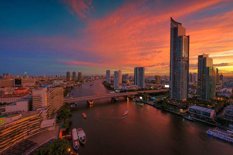 Chao Phraya River at Sunset, Bangkok, Thailand Bangkok Chao Phaya River City Cityscape Downtown Skyscrapers Thailand Architecture Building Exterior Buildings Built Structure City Cityscape Cloud - Sky Dusk Illuminated Modern Night No People Outdoors Road Sky Skyscraper Sunset Taksin Bridge Travel Destinations Urban Skyline
