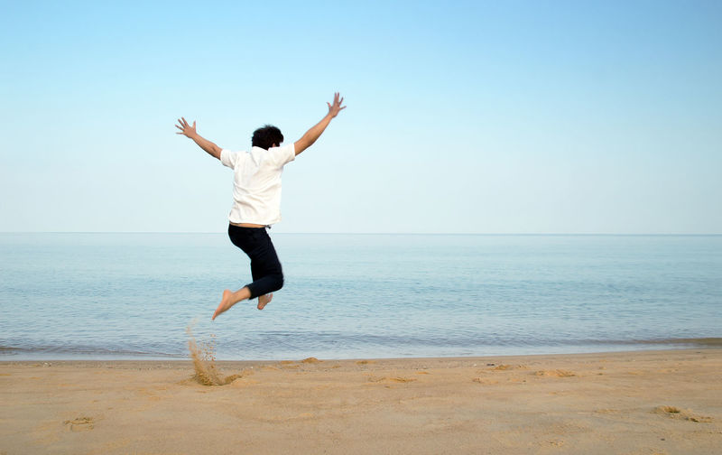 Full length rear view of man jumping on beach