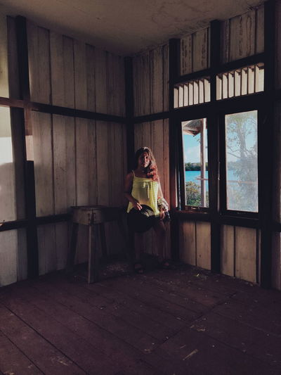 Woman sitting in abandoned building