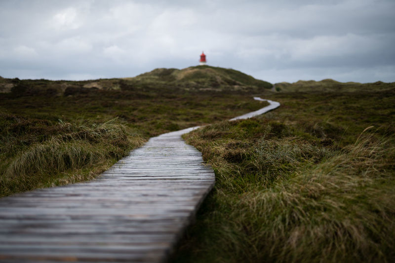 Path to lighthouse on amrum island germany after the rain on cloudy day