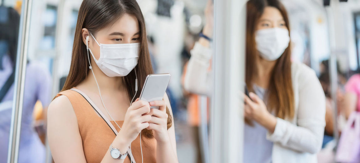 Woman wearing mask using mobile phone in train