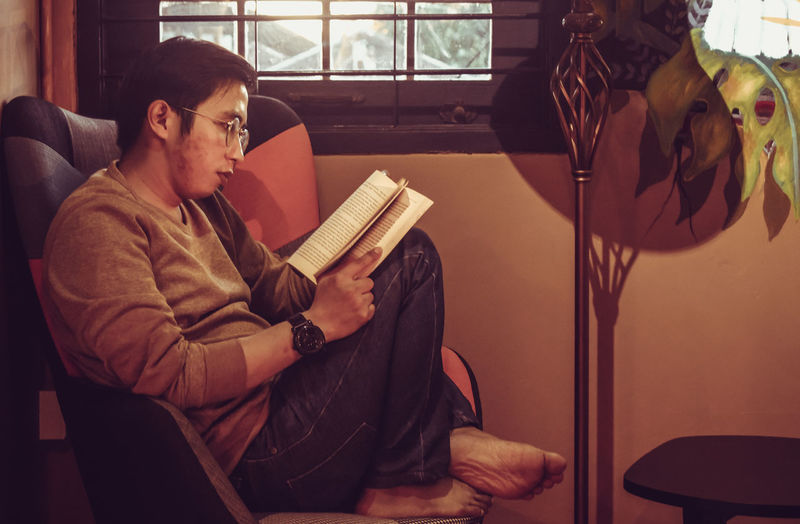 Young man reading book at home