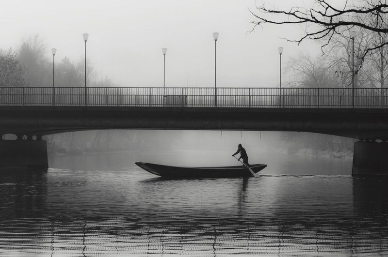 Silhouette Man Sailing Boat On Lake Against Bridge