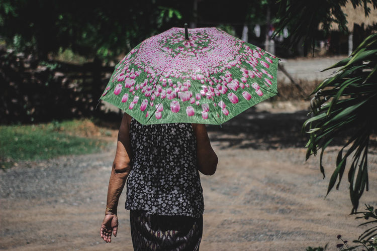 Rear view of woman with umbrella walking on footpath