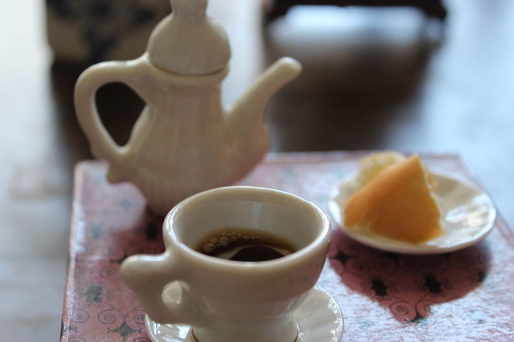Close-Up Of Black Coffee With Food On Table