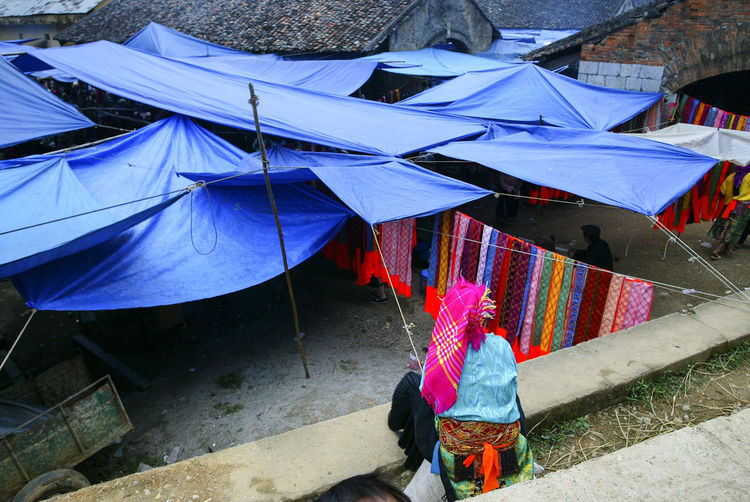 Rear view of person sitting by tarpaulins
