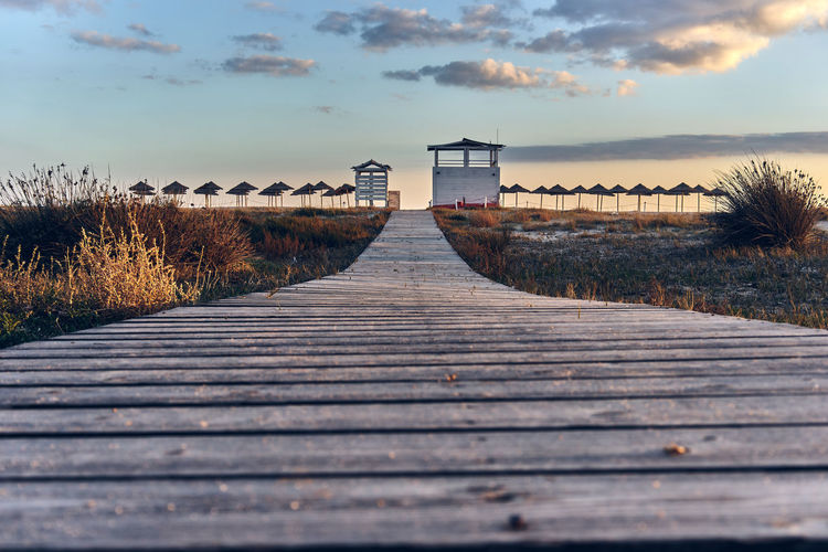 Boardwalk leading towards sea against sky