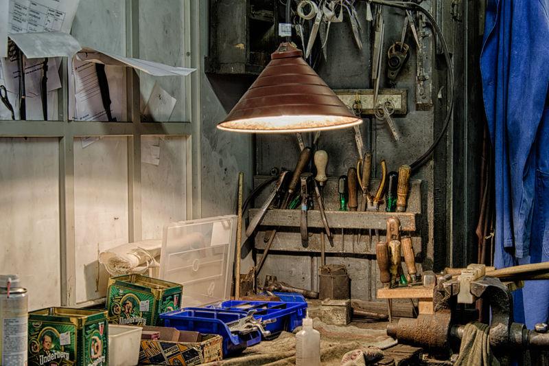 Illuminated pendant light over hand tools in workshop
